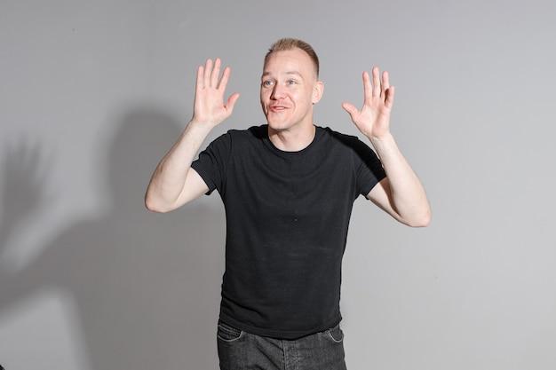 Grappige mens die zijn handen omhoog houdt en glimlacht in studio op witte achtergrond, backstage van een fotosessie