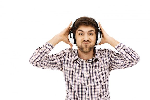 Grappige mens geniet van het luisteren van muziek in de koptelefoon