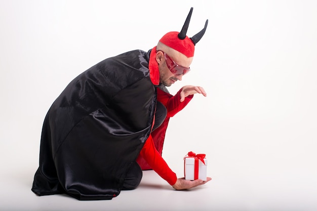 Grappige mens in halloween-kostuum en giftbox die op wit wordt geïsoleerd.