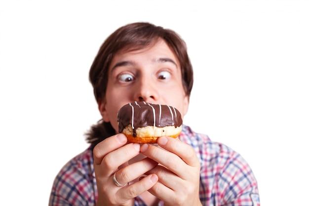 Grappige mens kijkt naar de chocoladedoughnut