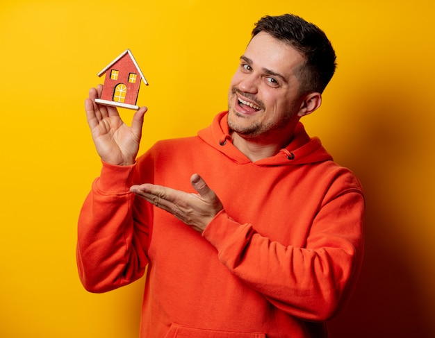 Grappige mens met stuk speelgoed huis op gele muur