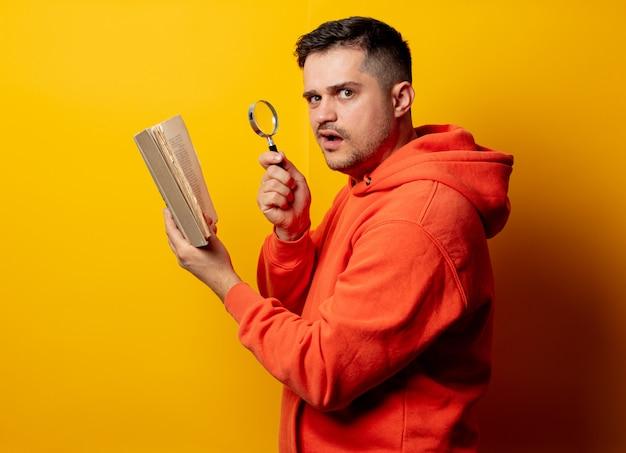 Grappige mens met vergrootglas en boek op gele muur
