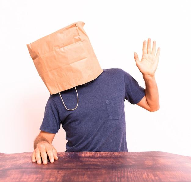 Grappige mens met zijn hoofd bedekt met een papieren zak die met zijn handen gebaart