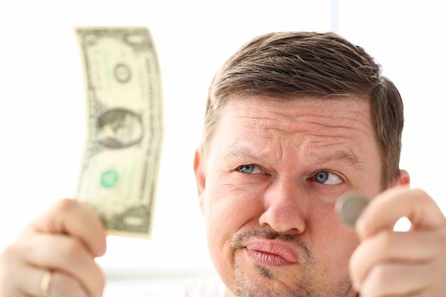 Grappige mensenholding in handendocument en muntstukmunt die wat goede oplossing proberen uit te vinden