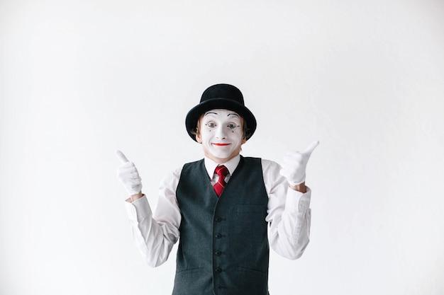 Grappige mime in zwarte hoed houdt zijn duimen omhoog