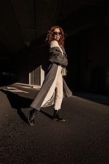 Grappige modieuze gelukkige vrouw met krullend haar en zonnebril in vintage lange jas en stijlvolle handtas wandelingen in de stad. stedelijke vrouwelijke herfststijl en gelukkige emoties