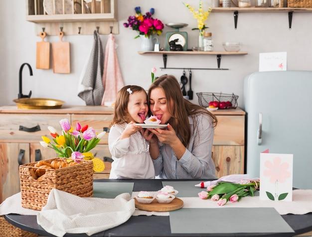 Grappige moeder en dochter die cupcake eten