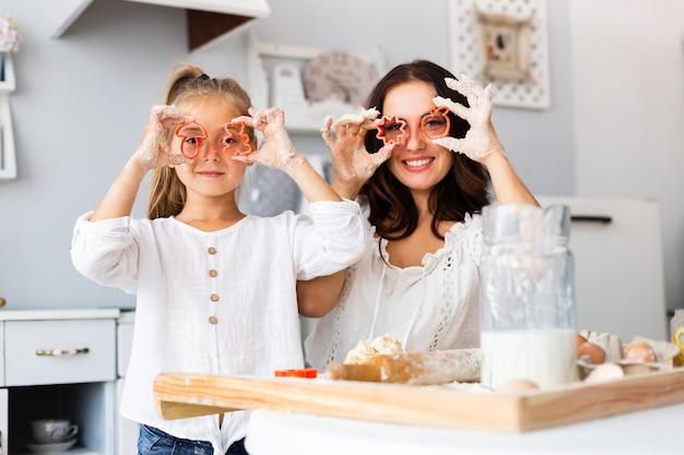 Grappige moeder en dochter die koekjesvormen gebruiken