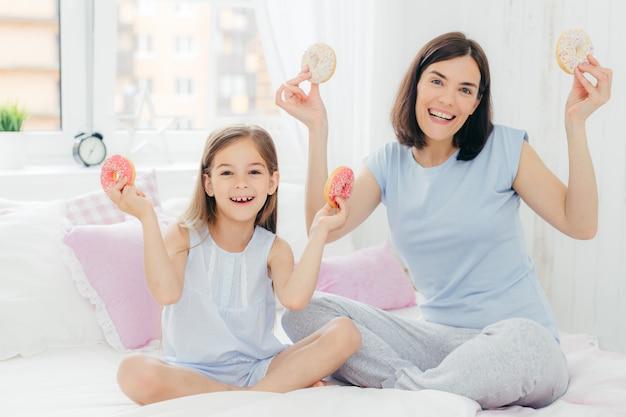 Grappige moeder en dochter gekleed in nachtkleding, hebben een goed humeur in de ochtend, houden smakelijke donuts vast