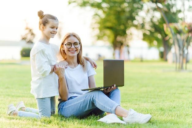 Grappige moeder en dochter met moderne laptop buitenshuis