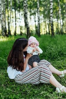 Grappige moeder met baby zittend op het gras