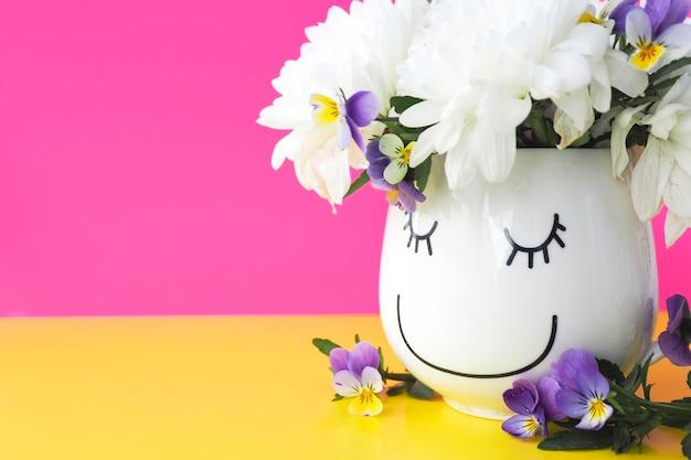 Grappige mok met een getekend gezicht met een boeket van chrysanten en viooltjes op een geelroze achtergrond. ruimte kopiëren.