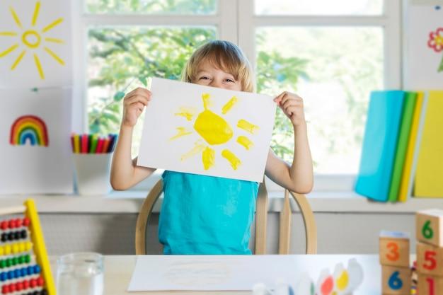 Grappige mooie gelukkige kindjongen tekent lachend met verf kind toont tekening van zon