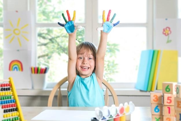 Grappige mooie gelukkige kindjongen toont handen vuil met verf kind trekt lachend met verf