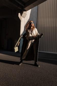 Grappige mooie jonge lachende vrouw met krullend haar in modieuze kleding kijken met een vintage jas, zonnebril, trui, schoenen en een handtas wandelingen in de stad op een zonnige dag. gelukkig meisje met een glimlach