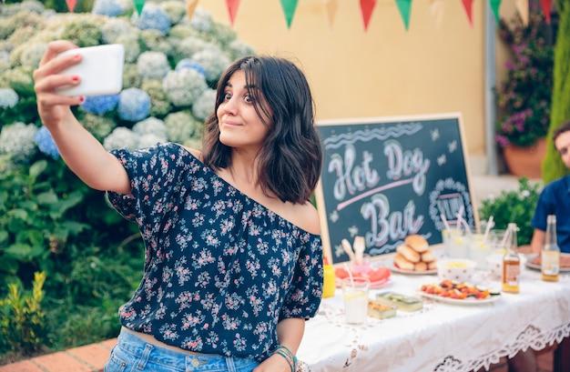 Grappige mooie jonge vrouw die een selfie maakt met haar smartphone voor de tafel, klaar om te eten in een zomerbarbecue in de buitenlucht