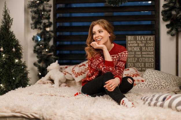 Grappige mooie jonge vrouw met een glimlach in een modieuze trui zit op het bed
