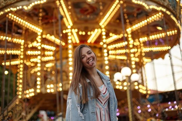 Grappige mooie jonge vrouw met lang haar, poseren over attracties in pretpark, knipoog geven en tong tonen