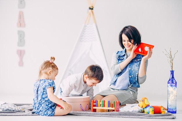Grappige mooie kinderen plezier maken met hun moeder in de witte kinderkamer. broer, zus en hun moeder spelen samen.