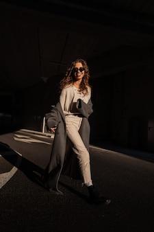 Grappige mooie lachende jonge vrouw met krullend haar in mode kleding met een lange jas, gebreide trui, broek, laarzen en zonnebril loopt op straat in het zonlicht en de schaduw. stedelijke stijl