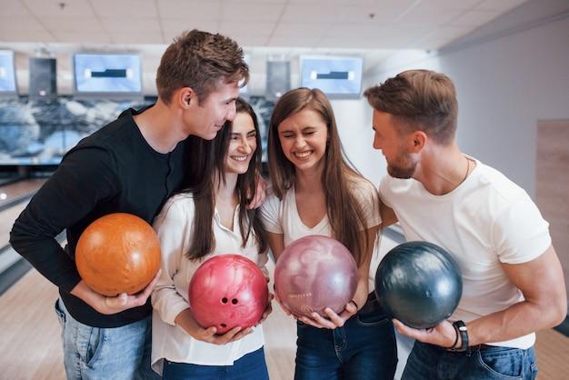 Grappige mop. jonge, vrolijke vrienden vermaken zich in het weekend in de bowlingclub