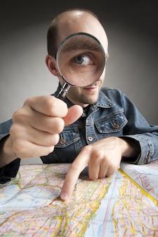 Grappige nerd-toerist die kaart met vergrootglas ontdekt