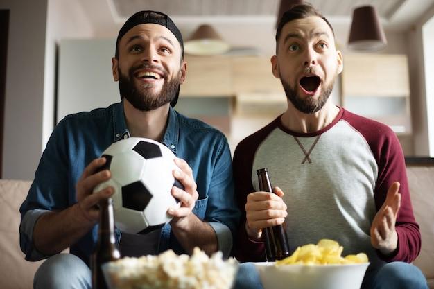Grappige opgewonden hipster bebaarde vrienden met snacks en bier kijken naar voetbal op tv zittend op de bank thuis. fans schreeuwen vanwege het winnen van hun team