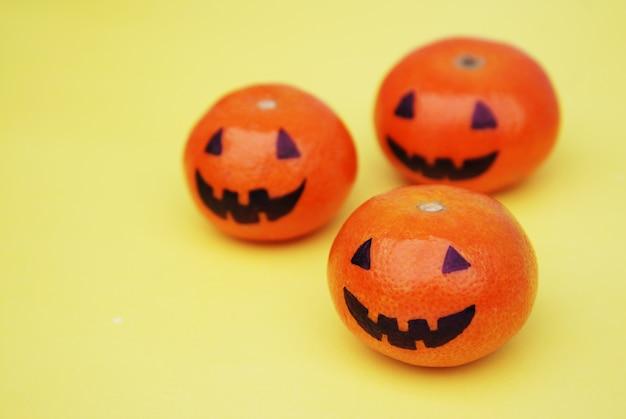 Grappige oranje mandarinstangerines pompoen geschilderd in de vorm van iconen van halloween op het geel