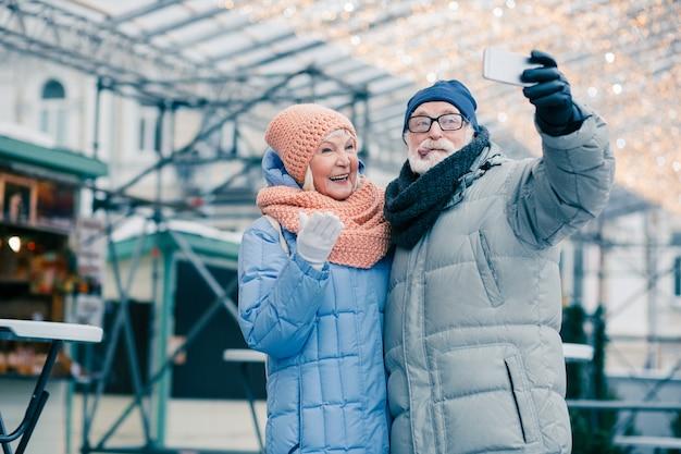 Grappige oudere man die zijn tong laat zien terwijl hij een selfie neemt met een lachende vrouw buiten in winterkleren