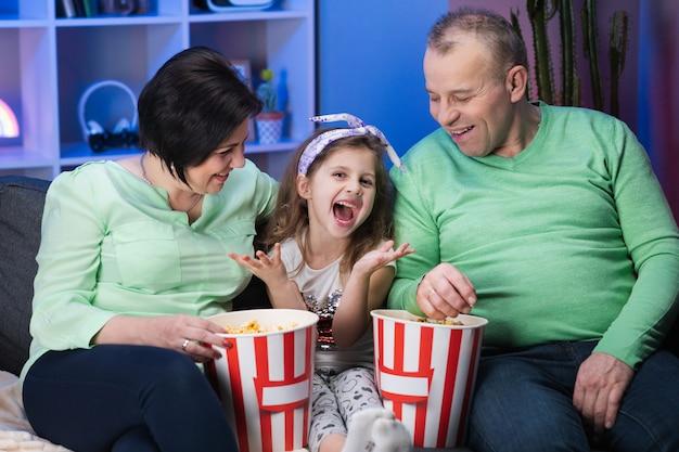 Grappige oudere oude familie en kleine kind kleindochter zit op de bank en tv kijken eten popcorn