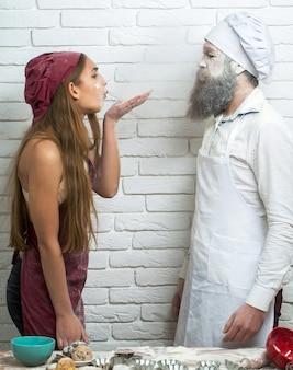 Grappige paar in keuken mooi meisje of mooie vrouw bestrooit bloem op knappe man kok of bakker gezicht baard en snor