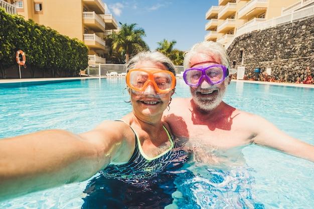 Grappige paar volwassen mensen nemen selfie foto's terwijl ze genieten en plezier hebben bij het zwembad in residentie