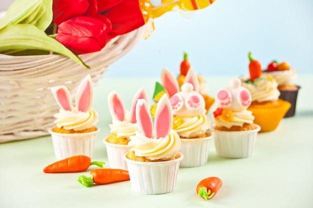 Grappige paashaas cupcake. feestelijke tafel voor pasen. mand met bloemen tulpen op de achtergrond.