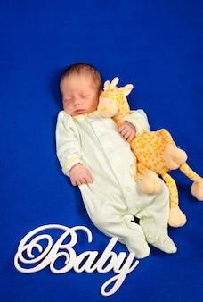 Grappige pasgeboren slaap op een blauwe deken kleine jongen in pyjama die een dutje doet