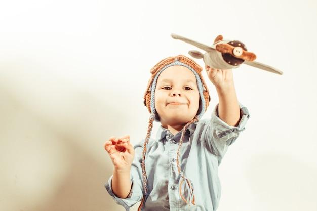 Grappige peuterjongen in gehaakte pilotenmuts die speelt met speelgoedvliegtuig van textiel