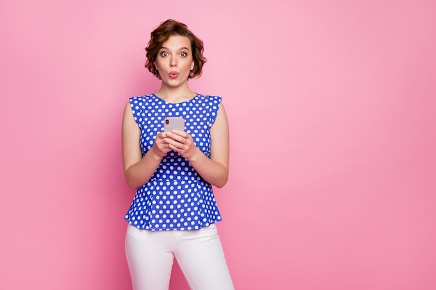 Grappige pin-up stijl jonge dame houdt telefoon geschokt reactie