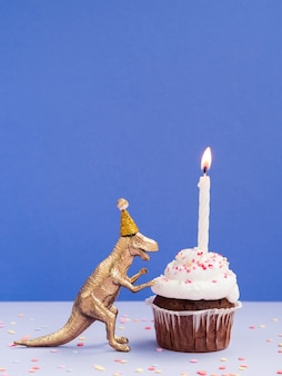 Grappige plastic dinosaurus en verjaardagsmuffin