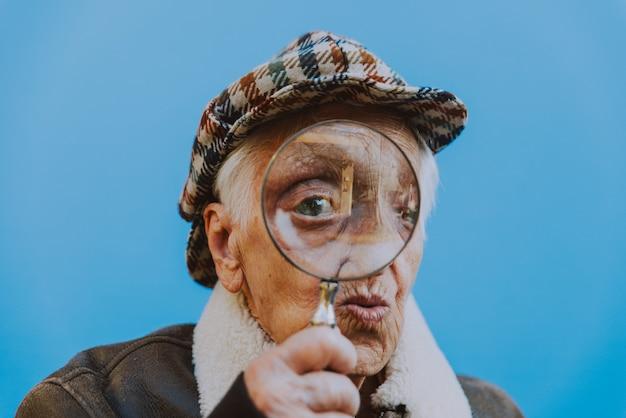 Grappige portretten met oude oma. senior vrouw die optreedt als een onderzoeker met de vergrotende lens