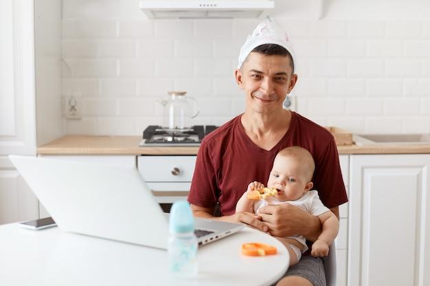 Grappige positieve aantrekkelijke brunette man freelancer dragen casual stijl kastanjebruin t-shirt en luier op zijn hoofd, werken en zorgen voor zijn dochtertje.