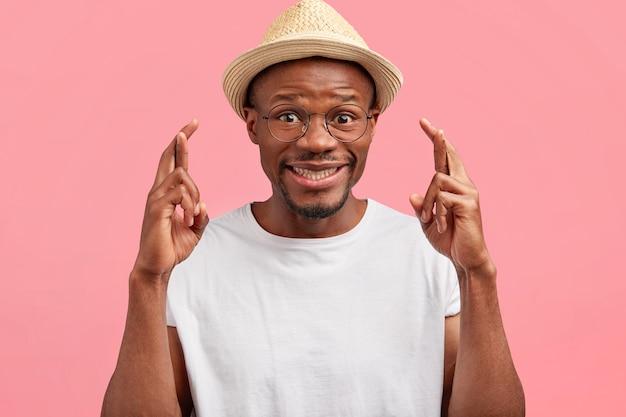 Grappige positieve afro-amerikaanse man van middelbare leeftijd kruist vingers