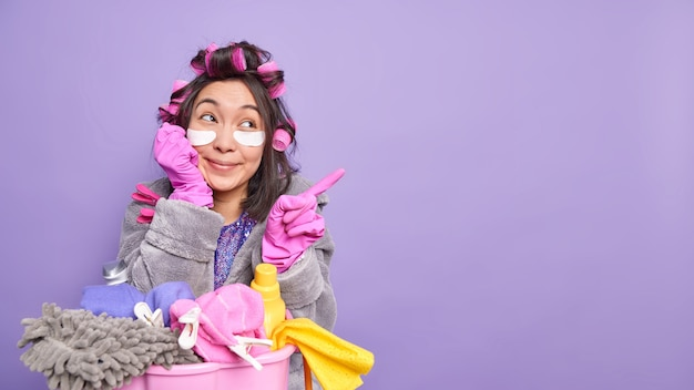 Grappige positieve jonge aziatische vrouw poseert in de buurt van zware wasmand draagt kamerjas en rubberen handschoenen geeft aan dat weg op kopieerruimte schoonheidsbehandelingen ondergaat geïsoleerd over paarse muur