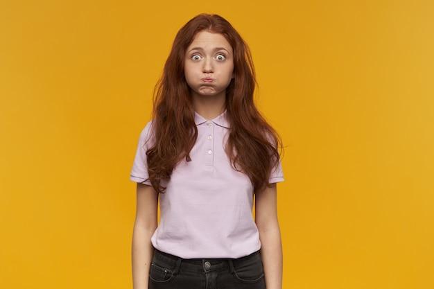 Grappige, positieve vrouw met lang gemberhaar. roze t-shirt dragen. mensen en emotie concept. hij blaast haar wangen, mond vol water. geïsoleerd over oranje muur