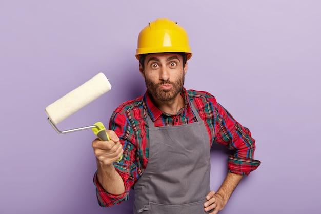 Grappige reparateur draagt veiligheidshelm, schort