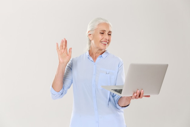 Grappige rijpe vrouw die laptop computer met behulp van die over wit wordt geïsoleerd