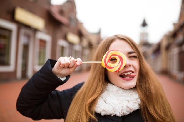 Grappige roodharige jonge vrouw met kleurrijke kerstsnoepjes op straat