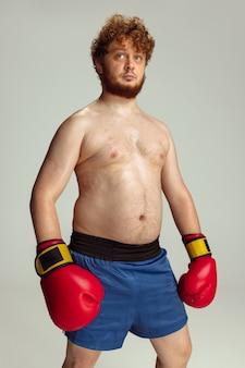 Grappige roodharige man in blauwe boksbroek en handschoenen geïsoleerd op grijs