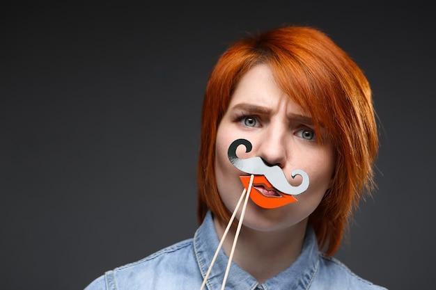 Grappige roodharige vrouw draagt nep snor en lippen
