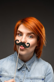 Grappige roodharige vrouw draagt nep snor