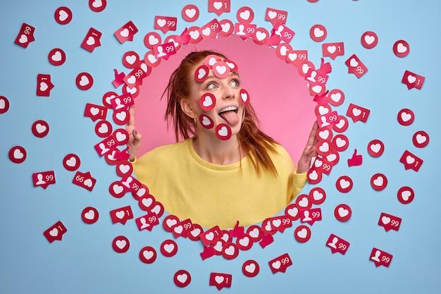 Grappige roodharige vrouw is blij met het krijgen van veel tarieven voor post, houdt van tekenknoppen in de vorm van een hart op het gezicht, emotionele reactie.