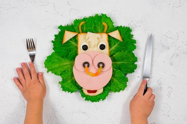 Grappige sandwich met eetbare stierensymbool van 2021 gemaakt van toast en worst op groene slablaadjes. de handen van kinderen houden een vork en een mes vast. ontbijtidee voor kinderen.
